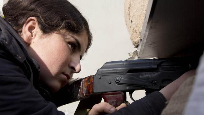 A female Kurdish fighter takes aim in Kobani, Syria. Picture: AP /Jake Simkin