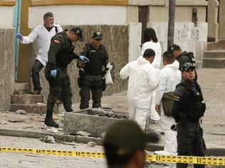Investigators inspect the site where a homemade bomb exploded near the Santamaria bull ring in Bogota, Colombia, Sunday, Feb. 19, 2017. The artefact was detonated just a few hours before a scheduled bullfight, killing a police officer and injuring several dozen bystanders. (AP Photo/Ricardo Mazalan)