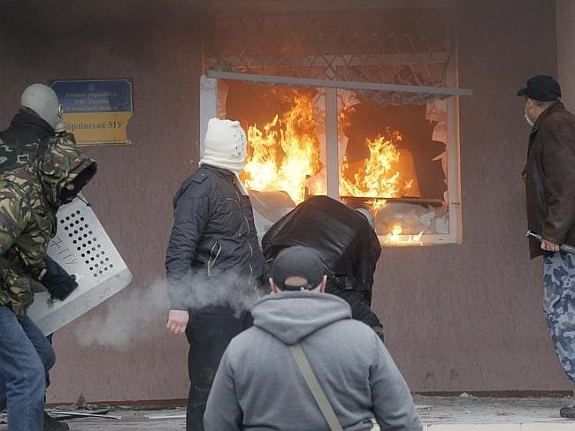 Up in flames ... Pro-Russian men attack a police station in the eastern Ukrainian town of Gorlivka. Picture: Efrem Lukatsky