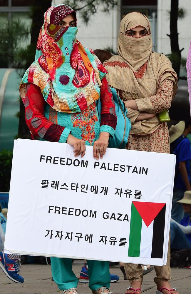 Not giving up ... demonstrators hold a placard denouncing Israel's air strikes in Gaza, during a rally near the Israeli embassy in Seoul. Picture: AFP