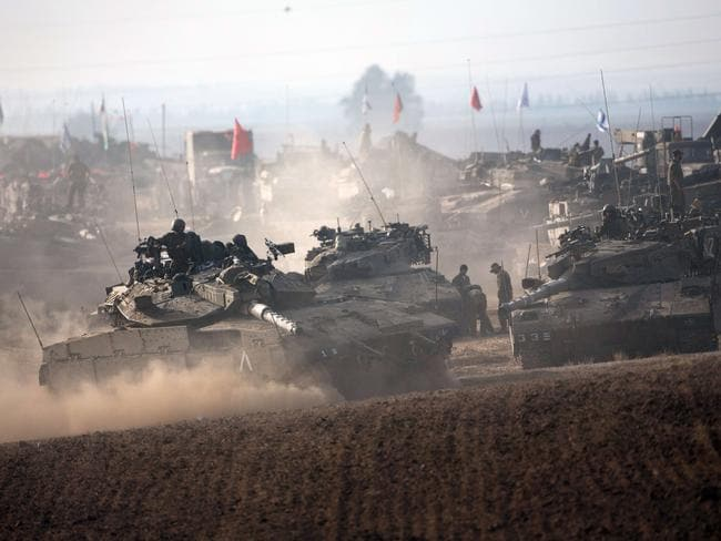 Massed strength ... Israeli soldiers work on their Merkava tanks in an army deployment area near Israel's border with the Gaza Strip.