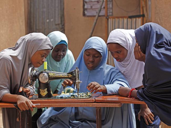 Maimuna, centre, speaks to classmates as she sews clothes during class at her school.