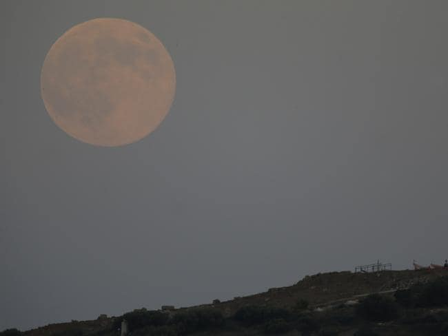 The moon appears above the ancient Temple of Poseidon as visitors watch it in Cape Sounio, about 68km south of Athens. AP Photo/Thanassis Stavrakis.