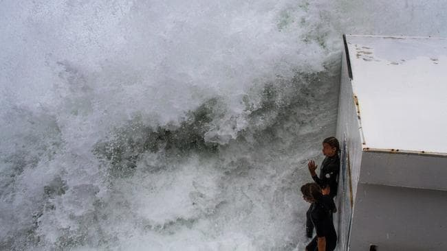 The two teens prepare to jump into the huge swell at Bronte Beach, Sydney, Australia. Picture: Bill Morris