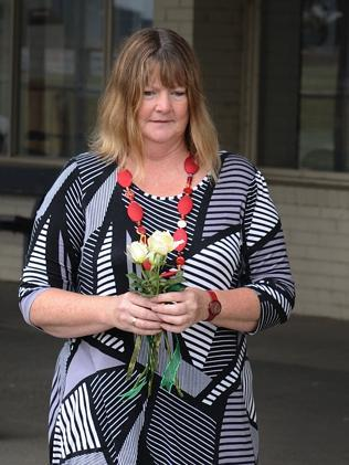 A woman arrives with flowers to leave at the oval where Luke died. Picture: Ellen Smith