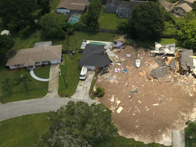 A sinkhole that started out the size of a small swimming pool and continued to grow has swallowed two homes in Florida. Picture: Luis Santana/Tampa Bay Times via AP