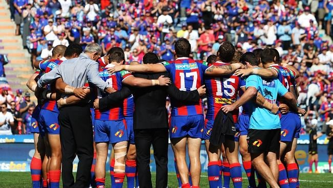 Newcastle players form a huddle in respect for injured player Alex McKinnon. Picture: Brett Costello
