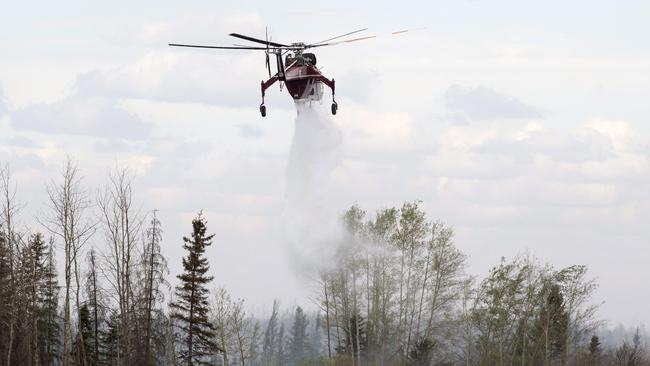 A helicopter d-rops water on hot spots along the highway. Picture: Ryan Remiorz/The Canadian Press.
