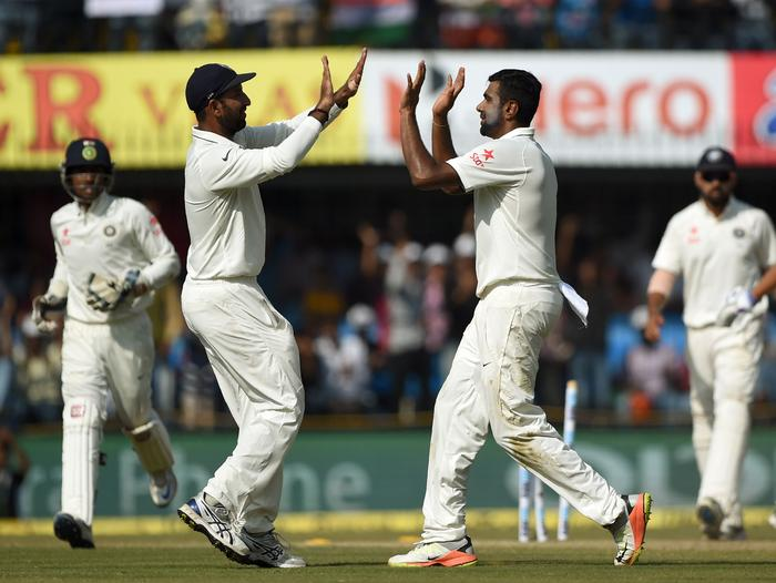 Ravichandran Ashwin (R) is congratulated by Cheteshwar Pujara after dismissing Ross Taylor.