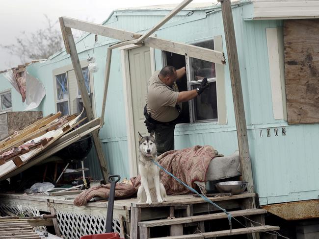 An official climbs through a window as he checks a home damaged by Hurricane Harvey on Sunday. Picture: Eric Gay/AP
