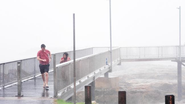 Cyclone chasers brave the elements and test their luck on the Nightcliff Jetty as Cyclone Marcus made its way to Darwin on Saturday morning. Picture: Justin Kennedy