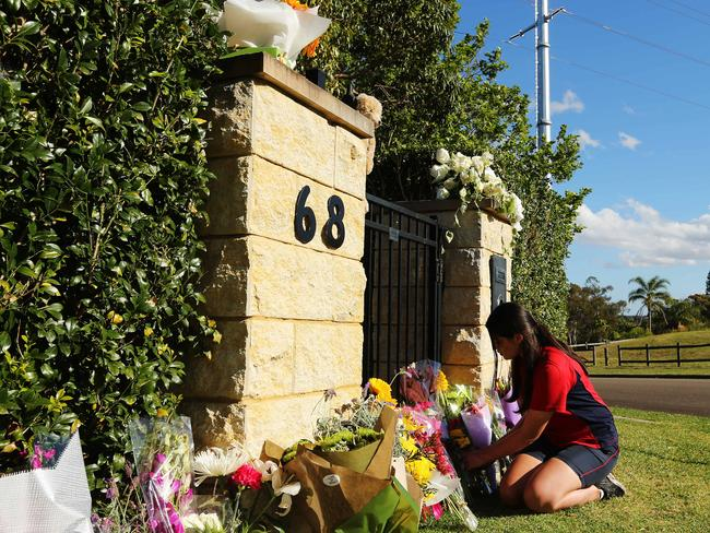 A woman adds flowers to the tributes outside the Davidson home after the family of four was found inside. Picture: News Corp.