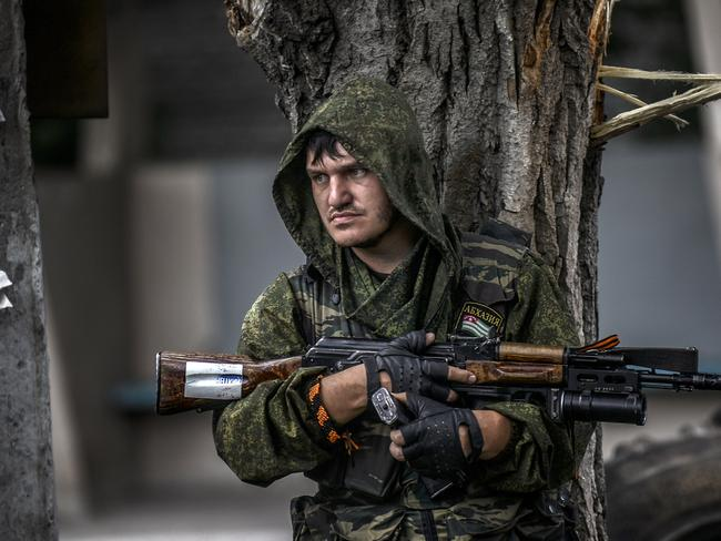 Edgy scenes ... a pro-Russian separatist holds his gun as he takes cover behind a tree at a checkpoint in Donetsk. Picture: Bulent Kilic