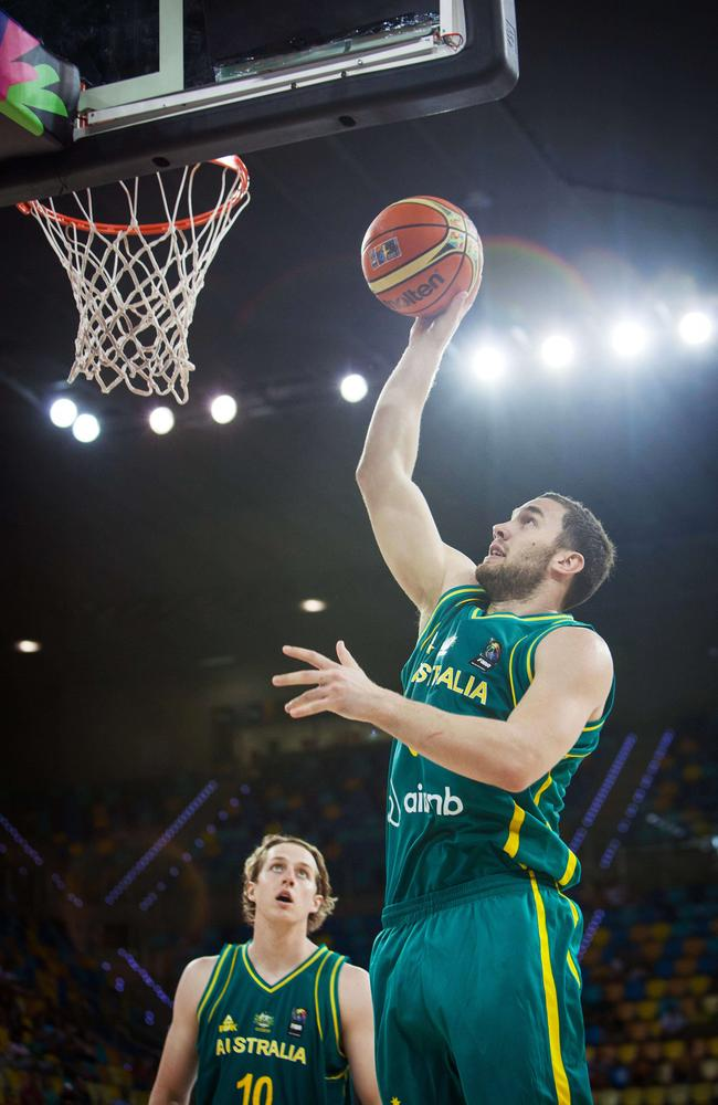 Australian guard Adam Gibson collects two points in front of forward Cameron Bairstow.