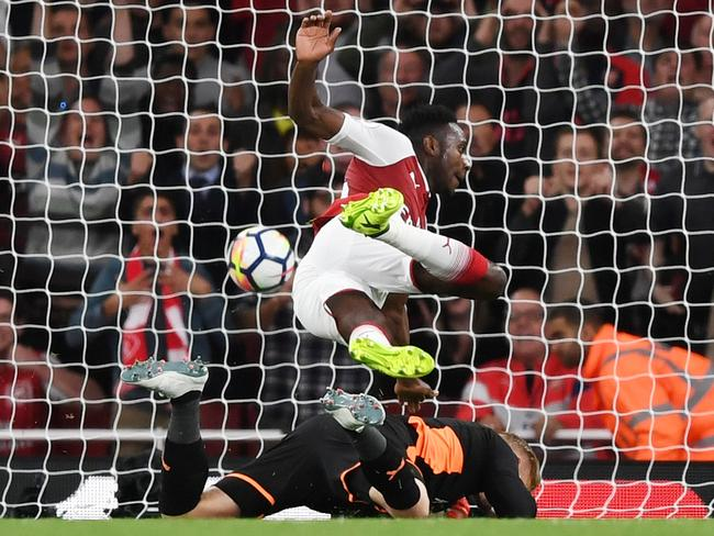 Danny Welbeck of Arsenal collides with Kasper Schmeichel of Leicester City as he scores his team's second goal.