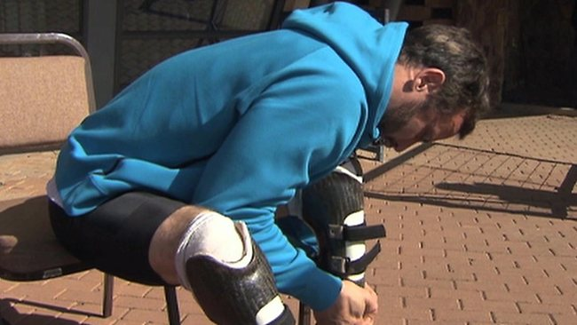 In this image taken from a video, Oscar Pistorius pulls on his carbon fibre running blades at the University of Pretoria.