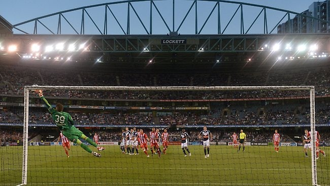 Victory goalkeeper Nathan Coe dives full stretch to brilliant save a free kick from Heart's Golgol Mebrahtu at Etihad Stadium. Picture: George Salpigtidis