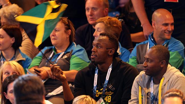 Usain Bolt waves the Jamaican flag as he watches the 'Reggae Girls' compete in the netball. Picture: Adam Head