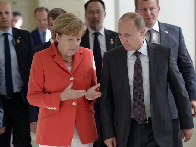 In agreement on investigation ... Russian President Vladimir Putin, right, and German Chancellor Angela Merkel.