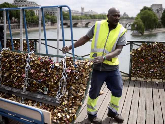 Removal ... a worker drags away a railing with thousands of lovelocks attached to it. Picture: AFP/Stephane De Sakutin