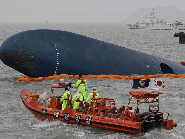 Scrambling to find more alive ... South Korean Coast Guard and rescue teams search as bad weather hampers their attempts. Picture: Chung Sung-Jun.