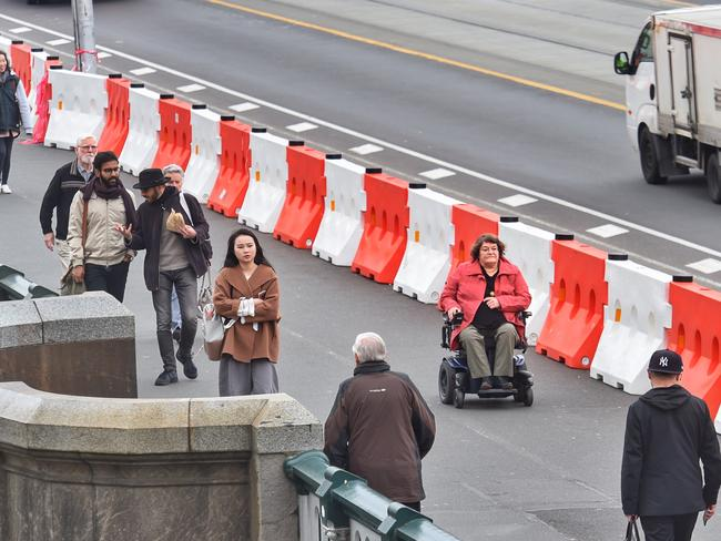 White and orange plastic bollards have been placed along the Princes Bridge to protect pedestrians from vehicles. Picture: Tony Gough