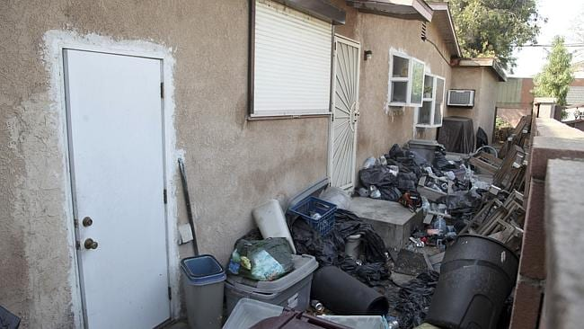 Hell hole ... trash is shown stacked against the home of William Buchman.