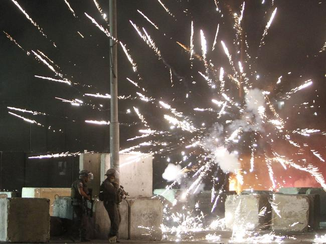 Fireworks display ... Israeli border guards take position as fireworks launched by Palestinian protesters lit the sky during clashes at the Qalandia checkpoint between Jerusalem and Ramallah.