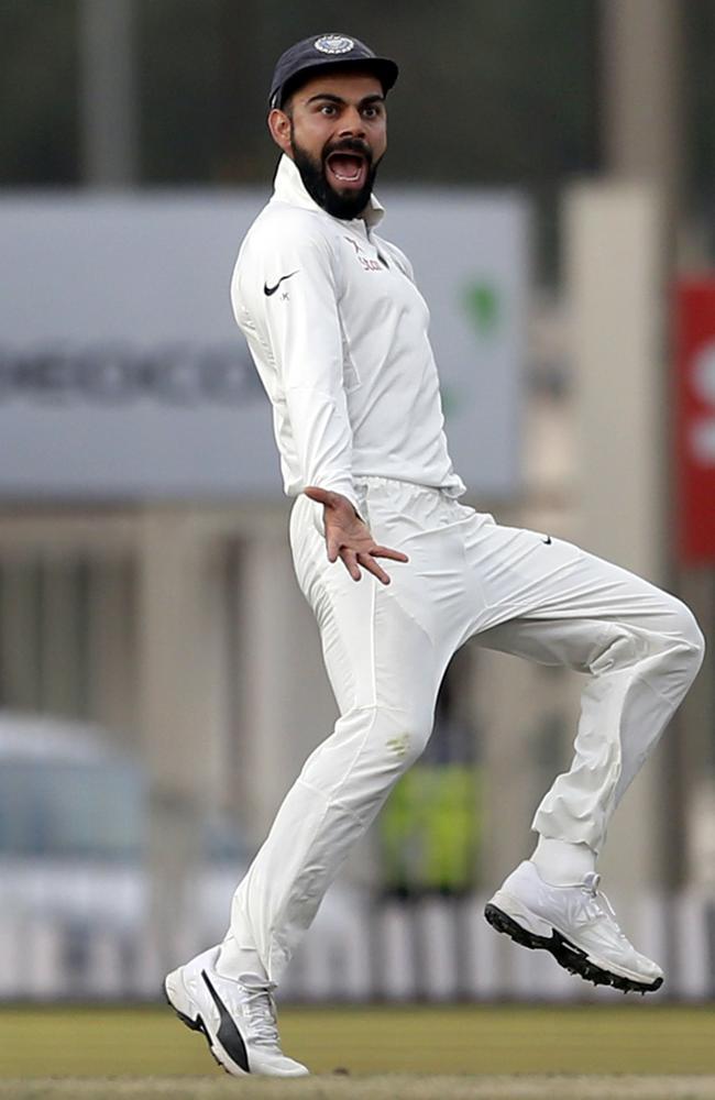 India's captain Virat Kohli gestures towards Australia's Matt Renshaw as he runs to celebrate the dismissal of David Warner.