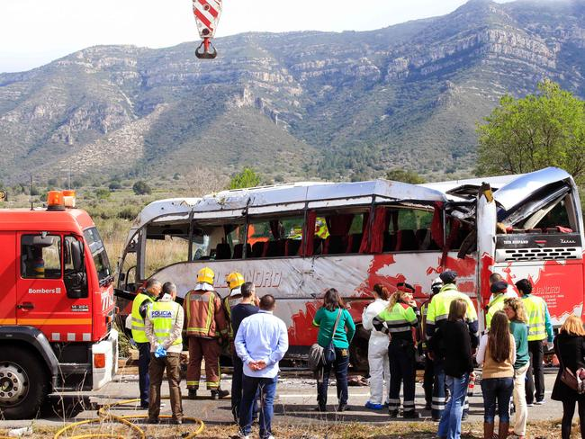 Tragic ... emergency personnel stand before the bus on the Spanish AP7 motorway near Freginals. Picture: AFP/Pau Barrena