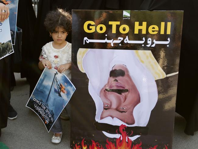 An Iranian girl stands among students staging a protest outside Tehran University on July 25, 2017 against Israeli security measures implemented at the al-Aqsa mosque compound in the Old City of Jerusalem. A portrait of Saudi King Salman is seen on the poster on the right. Israel removed metal detectors from a highly sensitive Jerusalem holy site after their installation triggered deadly violence, but Muslim officials said worshippers should continue a boycott for now. Israel installed metal detectors at entrances to the compound after an attack nearby that killed two policemen on July 14. / AFP PHOTO / ATTA KENARE