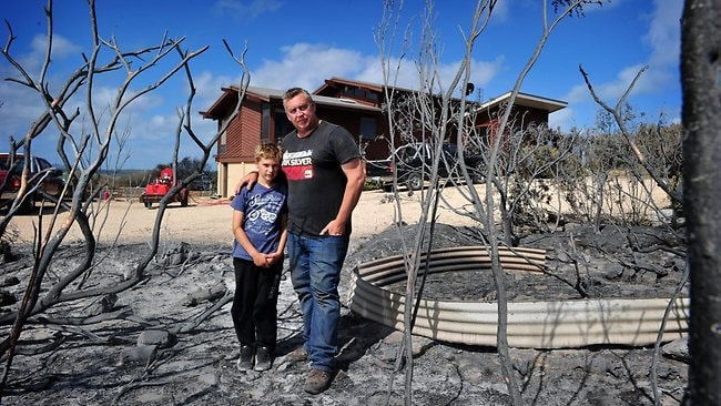 Thomas McNab and son Tommy, 9, stand where the fire came so close to burning their Sleaford Mere home. Picture: Mark Brake