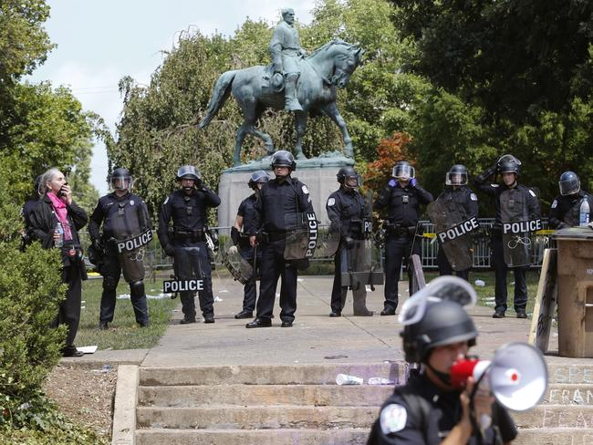 Virginia State Police in riot gear guard the statue of Robert E Lee. Picture: AP Photo/Steve Helber