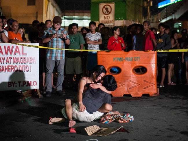 A woman embraces her dead husband, a suspected drug dealer, after he was shot by motorcycle riding vigilantes in Manila. Picture: Getty Images
