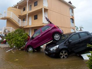 TOPSHOT - A photo taken on September 6, 2017 shows cars piled on top of one another in Marigot, near the Bay of Nettle, on the French Collectivity of Saint Martin, after the passage of Hurricane Irma. France, the Netherlands and Britain on September 7 sent water, emergency rations and rescue teams to their stricken territories in the Caribbean hit by Hurricane Irma, which has killed at least 10 people. The worst-affected island so far is Saint Martin, which is divided between the Netherlands and France, where eight of the 10 confirmed deaths took place. / AFP PHOTO / Lionel CHAMOISEAU
