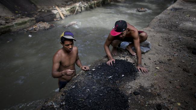 Men sort through the debris they pulled up from the bottom of the polluted Guaire River, in search of pieces of gold and anything of value to sell in Caracas, Venezuela. Picture: AP/Ariana Cubillos