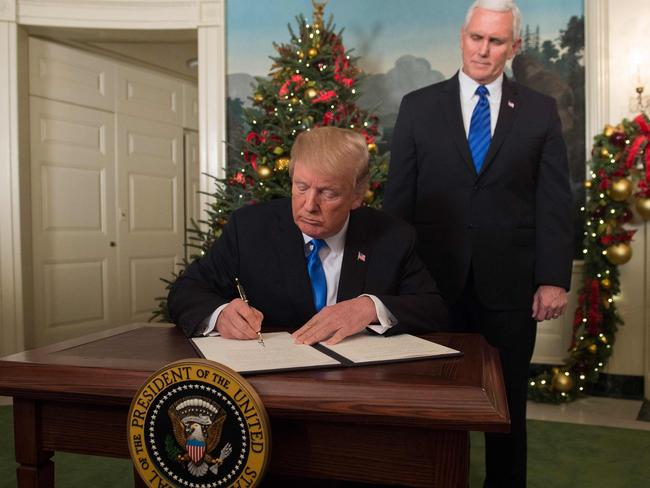 Mr Trump signs a proclamation after he delivered a statement on Jerusalem from the Diplomatic Reception Room of the White House in Washington, as Vice President Mike Pence looks on. Picture: Sael Loeb/AFP