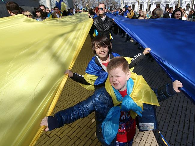 Opposite end ... pro-European Maidan supporters hold a large Ukrainian flag during a rally in Odessa. Picture: ALEXEY KRAVTSOV