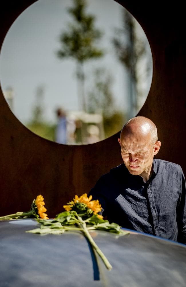 A relative puts flowers on a new memorial to commemorate MH17 victims. Picture: AFP/Remko de Waal