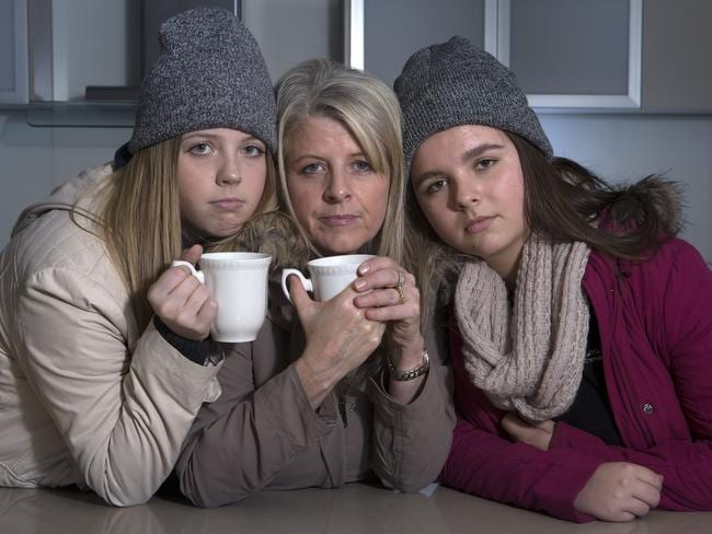 Thousands of Australians have felt the pinch of power prices this winter, and have been forced to leave their heating off. Robyn Svojtka and her daughters Bella and Holly rug up indoors saving electricity. Picture: Sarah Matray