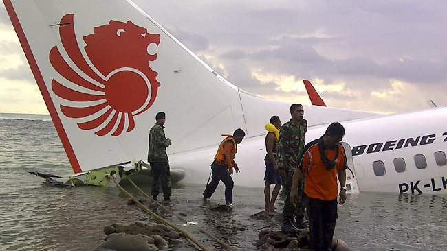 In this photo released by Indonesia's National Rescue Team, rescuers stand near the wreckage of a crashed Lion Air plane in Bali, Indonesia.