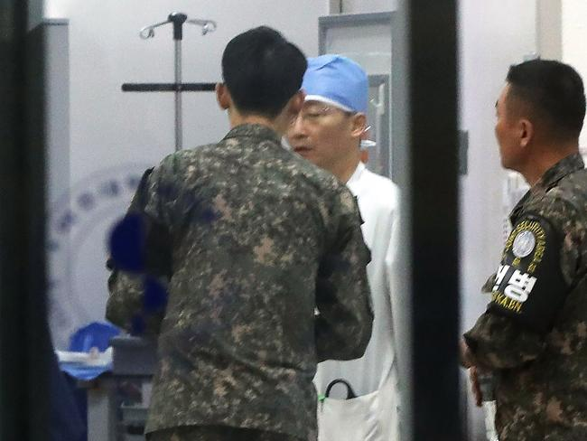 South Korean military officers, wearing armbands of the Joint Security Area of Panmunjom, talk with a doctor at a hospital in Suwon, south of Seoul. Picture: AFP/Yonhap