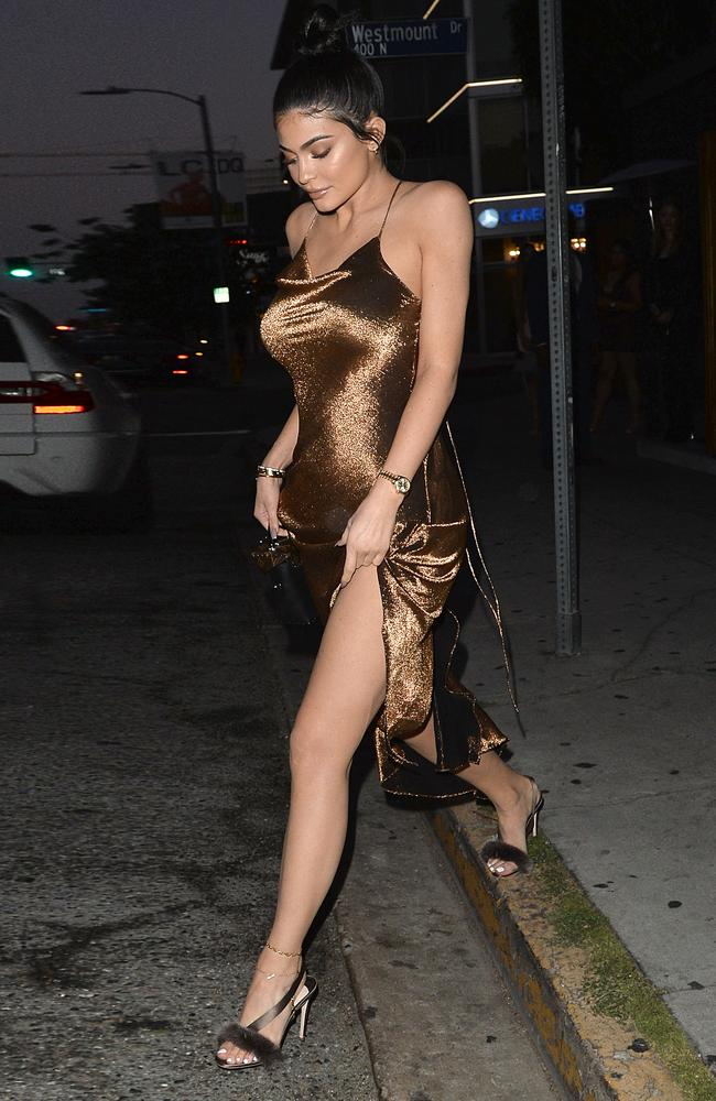 Kylie Jenner shows off her toned legs in the revealing bronze dress.
