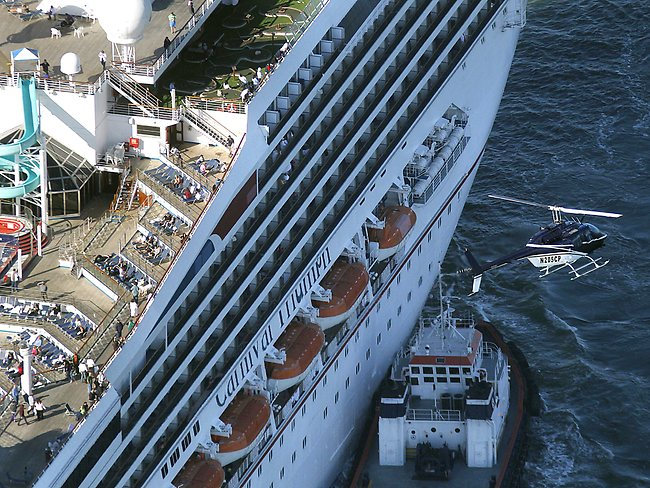 A helicopter flies above as the disabled Carnival Lines cruise ship Triumph is towed to harbor off Mobile Bay. Picture: AP