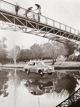 University students hang a FJ Holden motor car from Adelaide University footbridge, as part of a Prosh week stunt in 1971. Only wish we had the next photo in this sequence.