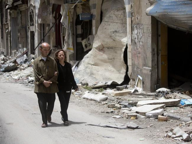 Zeinat Akhras and her brother Ayman walk to from home to a church in Homs, Syria. Over the course of the 700-day blockade, Zeinat's world shrunk to her living room and her kitchen. She survived reading books, eating plants — and refusing to look in the mirror, because seeing her withered state might break her spirit. Picture: AP