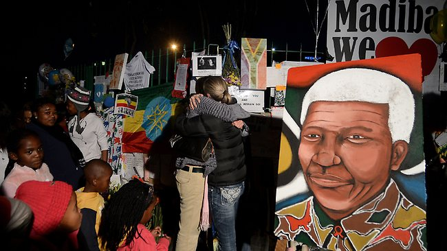 People stand near portraits of Nelson Mandela and messages left for him outside the Medi Clinic Heart hospital in Pretoria.