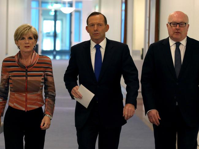 Tough decisions: Tony Abbott (centre) on his way to yesterday's press conference with foreign minister Julie Bishop and Attorney General George Brandis. Photo: AFP/Prime Minister's Office.