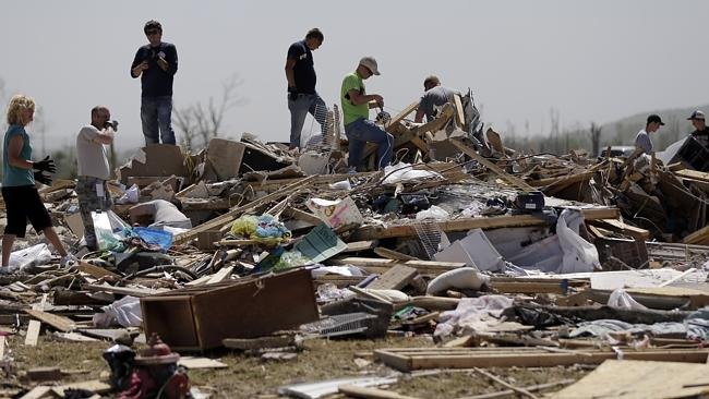 Residents and friends sift through debris after a tornado struck the area, Monday, April