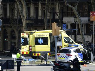 A policemen and a medical staff member stand past police cars and an ambulance in a cordoned off area after a van ploughed into the crowd, injuring several persons on the Rambla in Barcelona on August 17, 2017. / AFP PHOTO / Josep LAGO